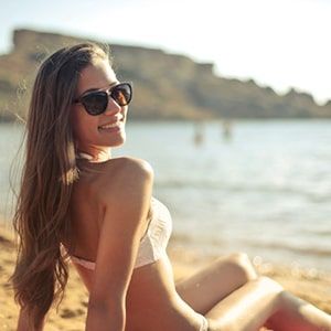 woman sunbathing in seaside with healthy and soft hair wearing bikini